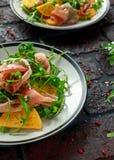 与芝麻菜、帕尔马火腿、橄榄油和草本的新鲜的鲜美柿子沙拉 秋天,冬天健康食物 免版税库存图片