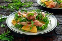 与芝麻菜、帕尔马火腿、橄榄油和草本的新鲜的鲜美柿子沙拉 秋天,冬天健康食物 图库摄影