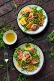 与芝麻菜、帕尔马火腿、橄榄油和草本的新鲜的鲜美柿子沙拉 秋天,冬天健康食物 库存照片