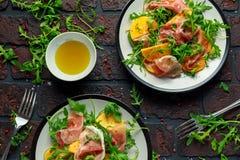 与芝麻菜、帕尔马火腿、橄榄油和草本的新鲜的鲜美柿子沙拉 秋天,冬天健康食物 库存图片
