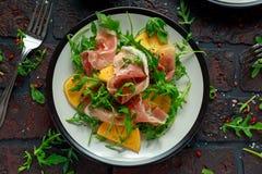 与芝麻菜、帕尔马火腿、橄榄油和草本的新鲜的鲜美柿子沙拉 秋天,冬天健康食物 免版税图库摄影