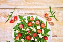 与芝麻菜、草莓、希腊白软干酪和坚果的新鲜的沙拉 库存图片