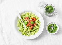 与芝麻菜pesto和西红柿的面团penne在轻的背景 库存图片