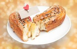 与芝麻和卡片银行票据的可口在t的面包和心脏 免版税库存图片