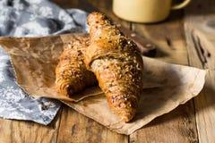与芝麻籽的全麦新月形面包在木厨房用桌,毛巾,搪瓷杯子上 库存图片
