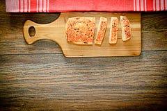 与芝麻籽的切的面包在一个木板 免版税库存照片