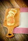 与芝麻籽的切的面包在一个木板 免版税库存图片