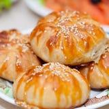 与芝麻籽的小圆面包samosa在欢乐桌上 库存照片