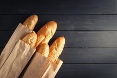 与芝麻籽的法国长方形宝石在黑木背景 免版税库存图片