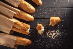 与芝麻籽的法国长方形宝石在黑木背景 免版税库存照片