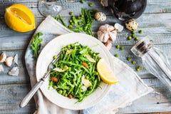 与芝麻菜、乳酪、杏仁、柠檬和橄榄的新鲜的蔬菜沙拉 免版税库存照片
