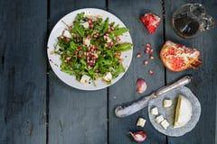 与芝麻菜、希腊白软干酪和石榴的沙拉在土气木头 免版税图库摄影