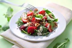 与芝麻菜、草莓、山羊乳干酪和核桃的沙拉 免版税库存照片