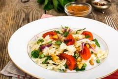 与芝麻菜、鸡、豌豆、葱和蕃茄的意大利面制色拉 免版税图库摄影