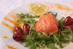 与芝麻菜和葡萄的三文鱼 免版税库存照片
