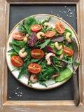 与芝麻菜和蕃茄虾的自创沙拉用在一块白色板材的雀跃 库存照片