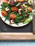与芝麻菜和蕃茄虾的自创沙拉用在一块白色板材的雀跃 免版税库存照片