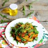 与芝麻菜和香料的切的烤土豆在一块白色板材和餐巾,一个瓶子橄榄油,在葡萄酒木桌上的叉子 库存图片