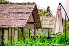 与芦苇漂浮在河的屋顶和大阳台的小木客舱 库存图片