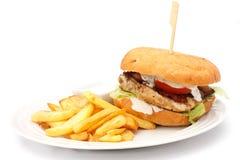 与芯片的烤鸡汉堡在白色板材 库存照片