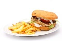 与芯片的烤鸡汉堡在白色板材 图库摄影