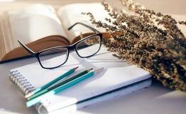 与花、书、玻璃和书写用具的静物画 免版税库存照片