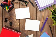 与花、供应和两个空白的照片框架的办公室桌 免版税库存图片