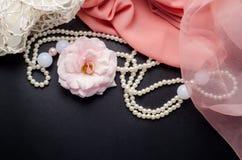 与花、珍珠项链和桃红色织品的抽象秀丽装饰背景在黑桌上 图库摄影