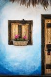 与花、蓝色墙壁和门的木窗口与挂锁,浸泡 免版税库存图片
