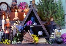 与花、蜡烛和不可思议的瓶的开放书在巫婆桌上 免版税库存照片