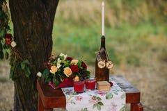 与花、蜡烛和箱子花束的仪式桌婚戒的 库存照片