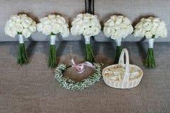 与花冠的5朵白玫瑰花束和玫瑰花瓣篮子  免版税库存图片