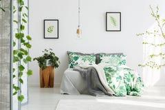 与花卉卧具的加长型的床 免版税图库摄影