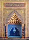 与花卉样式、蓝色土耳其陶瓷砖和阿拉伯书法,开罗,埃及的金黄华丽被成拱形的米哈拉布适当位置 库存照片