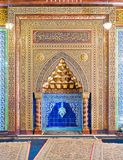 与花卉样式、蓝色土耳其陶瓷砖和阿拉伯书法,开罗,埃及的金黄华丽被成拱形的米哈拉布适当位置 免版税图库摄影