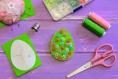 与花卉样式的可爱的复活节彩蛋装饰 毛毡蛋装饰,剪刀,纸模板,螺纹,在紫色木桌上的顶针 免版税库存图片