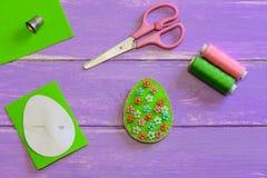 与花卉样式的复活节彩蛋装饰 毛毡蛋装饰,剪刀,纸模板,螺纹,在紫色木背景的顶针 免版税图库摄影