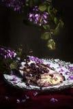 与花卉装饰的苹果计算机和莓果蛋糕在焦点 免版税库存图片