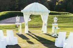 与花和Ñ  andle装饰的婚礼曲拱在晴天 免版税库存图片