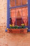 与花和五颜六色的帷幕的明亮的蓝色窗口在红砖墙壁 免版税库存照片