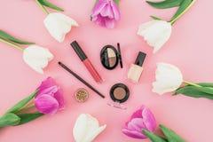 与花和化妆用品的构成在桃红色背景 顶视图 平的位置 家庭女性书桌 图库摄影