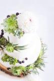 与花和多汁植物的典雅的婚宴喜饼 免版税库存照片