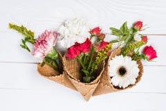 与花和奶蛋烘饼锥体的美好的花卉构成在白色木背景 免版税库存照片