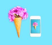 与花和智能手机的冰淇凌在蓝色五颜六色 免版税库存图片