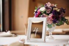 与花和标志数字的婚礼桌 免版税库存图片