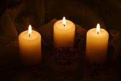 与花和欢乐桌布的蜡烛 免版税库存照片
