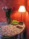 与花和灯光的壁角桌 免版税库存图片