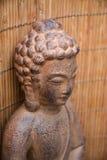 与花和禅宗石头的布朗菩萨雕象 库存图片