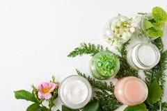 与花和绿叶的天然化妆品产品在白色背景 秀丽产业,拷贝空间 库存照片