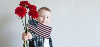 与花和美国国旗的孩子 库存图片